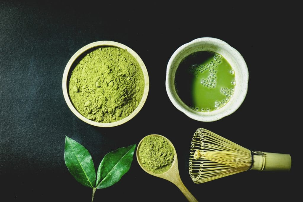 Green matcha powder with a chasen.